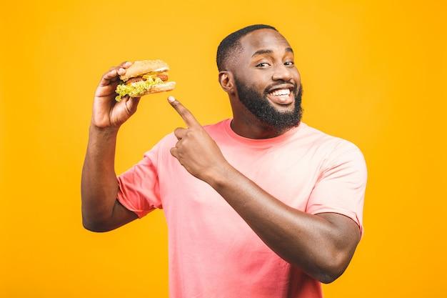 Młody amerykanina afrykańskiego pochodzenia mężczyzna łasowania hamburger odizolowywający nad kolor żółty ścianą.