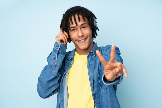Młody amerykanina afrykańskiego pochodzenia mężczyzna na błękit ściany słuchającej muzyce i śpiewie