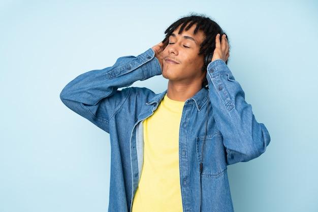 Młody amerykanina afrykańskiego pochodzenia mężczyzna na błękit ściany słuchającej muzyce i tanu