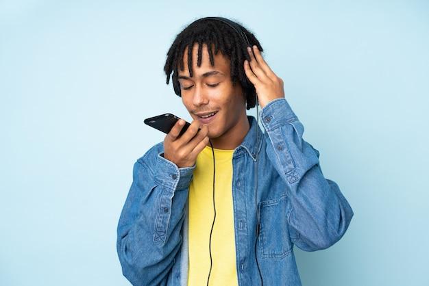 Młody amerykanina afrykańskiego pochodzenia mężczyzna na błękit ściany słuchającej muzyce z telefonem komórkowym i śpiewem