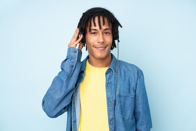 Młody amerykanina afrykańskiego pochodzenia mężczyzna na błękit ściany słuchającej muzyce