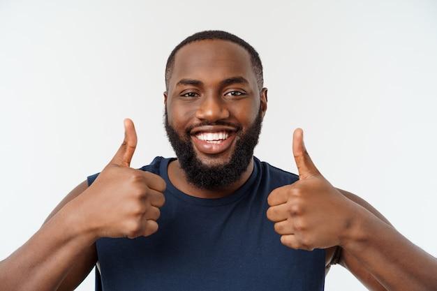 Młody amerykanina afrykańskiego pochodzenia mężczyzna nad odosobnioną jest ubranym sport odzieżą ono uśmiecha się z szczęśliwą twarzą patrzeje z kciukiem up.