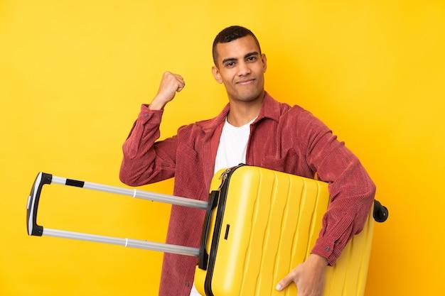Młody amerykanina afrykańskiego pochodzenia mężczyzna nad odosobnioną kolor żółty ścianą w wakacje z podróży walizką