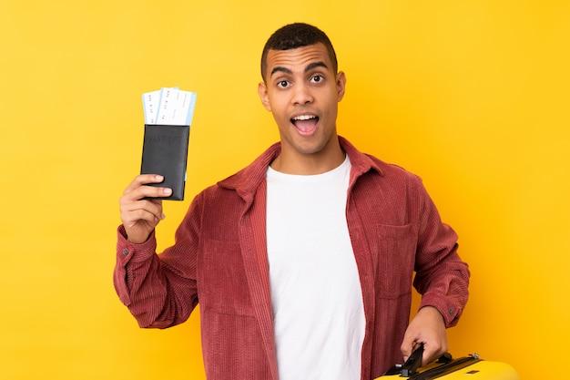 Młody amerykanina afrykańskiego pochodzenia mężczyzna nad odosobnioną kolor żółty ścianą w wakacje z walizką i paszportem i zaskakujący
