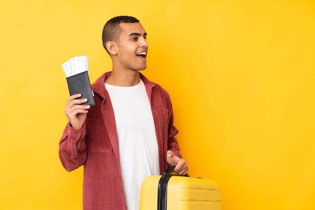 Młody amerykanina afrykańskiego pochodzenia mężczyzna nad odosobnioną kolor żółty ścianą w wakacje z walizką i paszportem