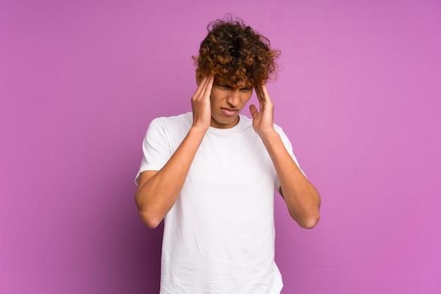 Młody amerykanina afrykańskiego pochodzenia mężczyzna nad odosobnioną purpury ścianą z migreną