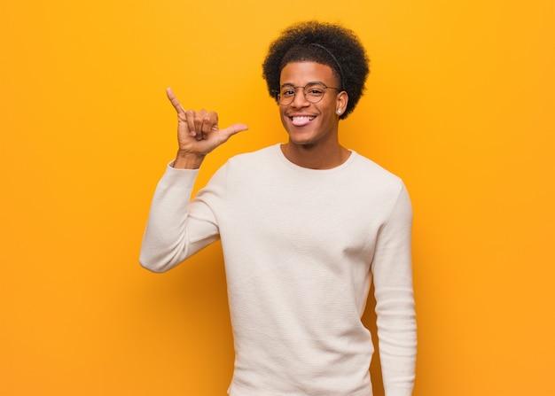 Młody amerykanina afrykańskiego pochodzenia mężczyzna nad pomarańczową ścianą robi rockowemu gestowi
