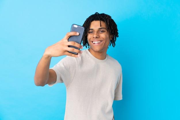 Młody amerykanina afrykańskiego pochodzenia mężczyzna nad ścianą