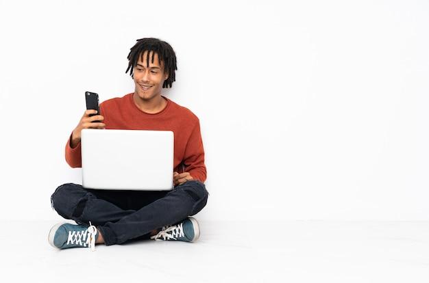 Młody amerykanina afrykańskiego pochodzenia mężczyzna obsiadanie na podłoga i działanie z jego laptopem robi selfie