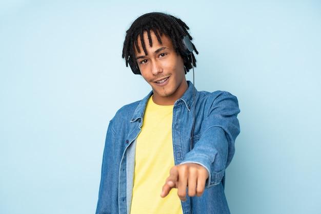 Młody amerykanina afrykańskiego pochodzenia mężczyzna odizolowywający na błękitnej słuchającej muzyce