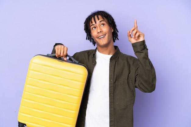 Młody amerykanina afrykańskiego pochodzenia mężczyzna odizolowywający na purpurach w wakacje z podróży walizką i wskazywać up
