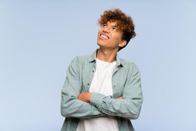 Młody amerykanina afrykańskiego pochodzenia mężczyzna przyglądający up podczas gdy ono uśmiecha się