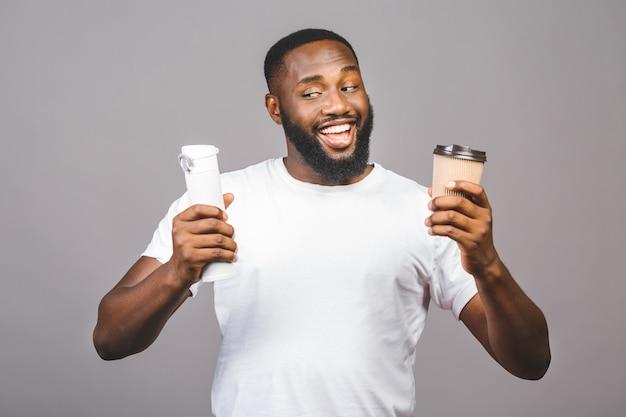 Młody amerykanina afrykańskiego pochodzenia mężczyzna robić wybiera między filiżanką kawy i przetwarza jeden pozycję nad odosobnionym szarym tłem.