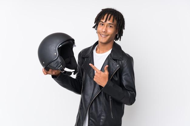 Młody amerykanina afrykańskiego pochodzenia mężczyzna trzyma motocyklu hełm odizolowywający na biel ścianie i wskazuje je