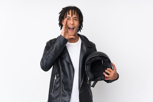 Młody amerykanina afrykańskiego pochodzenia mężczyzna trzyma motocyklu hełm odizolowywający na biel ścianie krzyczy z usta szeroko otwarty