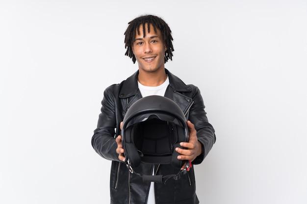 Młody amerykanina afrykańskiego pochodzenia mężczyzna trzyma motocyklu hełm odizolowywający na biel ścianie z szczęśliwym wyrażeniem