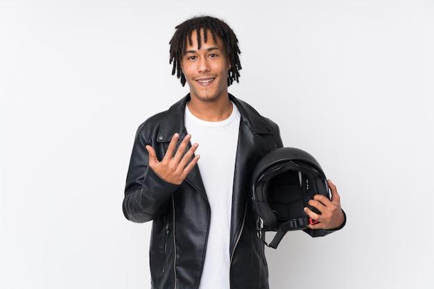 Młody amerykanina afrykańskiego pochodzenia mężczyzna trzyma motocyklu hełm odizolowywający na biel ścianie zaprasza przychodzić z ręką. cieszę się, że przyszedłeś
