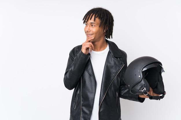 Młody amerykanina afrykańskiego pochodzenia mężczyzna trzyma motocyklu hełm odizolowywający na bielu myśleć pomysł i patrzeje stronę