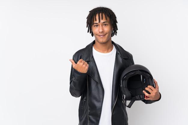 Młody amerykanina afrykańskiego pochodzenia mężczyzna trzyma motocyklu hełm odizolowywający na bielu wskazuje strona przedstawiać produkt
