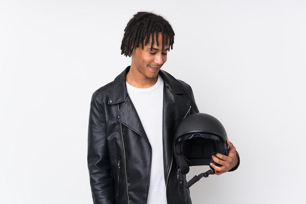 Młody amerykanina afrykańskiego pochodzenia mężczyzna trzyma motocyklu hełm odizolowywający na bielu z szczęśliwym wyrażeniem