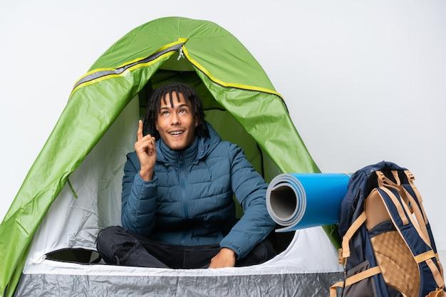 Młody amerykanina afrykańskiego pochodzenia mężczyzna wśrodku campingowego zielonego namiotu wskazuje w górę i zaskakujący