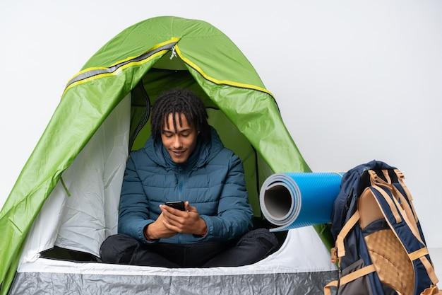 Młody amerykanina afrykańskiego pochodzenia mężczyzna wśrodku campingowego zielonego namiotu wysyła wiadomość z wiszącą ozdobą