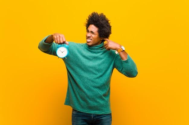 Młody amerykanina afrykańskiego pochodzenia mężczyzna z budzikiem przeciw pomarańczowym półdupkom
