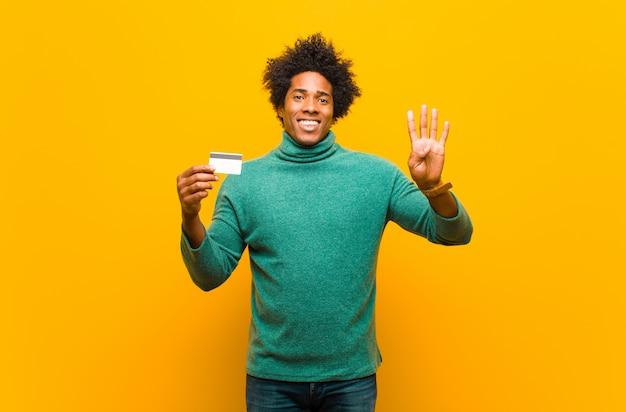 Młody amerykanina afrykańskiego pochodzenia mężczyzna z kartą kredytową przeciw pomarańczowemu bac