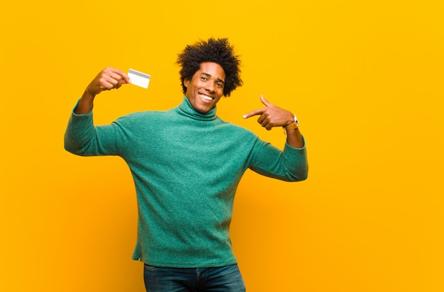 Młody amerykanina afrykańskiego pochodzenia mężczyzna z kartą kredytową