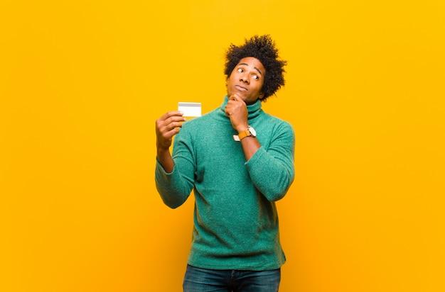 Młody amerykanina afrykańskiego pochodzenia mężczyzna z kredytowej karty pomarańcze