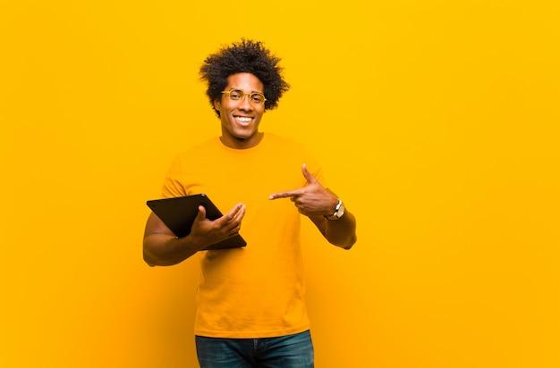 Młody amerykanina afrykańskiego pochodzenia mężczyzna z pastylką przeciw pomarańczowemu backgrou