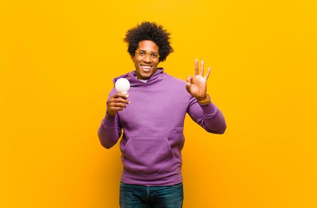 Młody amerykanina afrykańskiego pochodzenia mężczyzna z żarówką przeciw pomarańcze