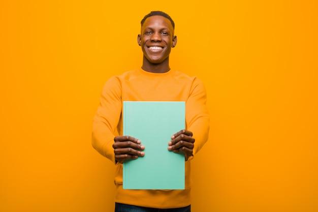 Młody amerykanina afrykańskiego pochodzenia murzyn przeciw pomarańcze ścianie z książką