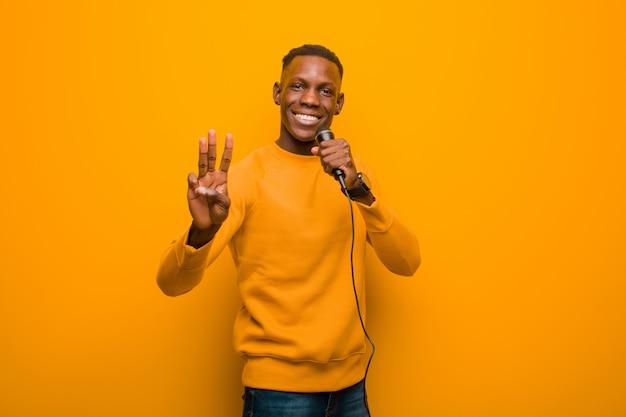 Młody amerykanina afrykańskiego pochodzenia murzyn przeciw pomarańcze ścianie z mikrofonem