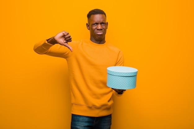 Młody amerykanina afrykańskiego pochodzenia murzyn przeciw pomarańcze ścianie z prezentem