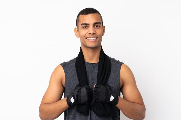 Młody amerykanina afrykańskiego pochodzenia sporta mężczyzna nad odosobnioną biel ścianą z sporta ręcznikiem