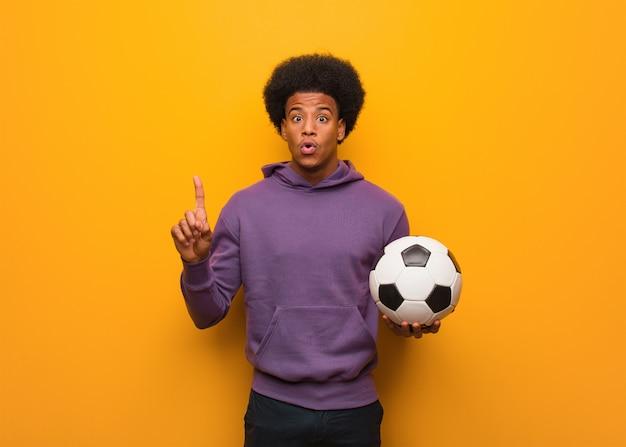 Młody amerykanina afrykańskiego pochodzenia sporta mężczyzna trzyma piłki nożnej piłkę ma doskonałego pomysł, pojęcie twórczość