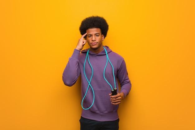 Młody amerykanina afrykańskiego pochodzenia sporta mężczyzna trzyma skakankę myśleć o pomysle