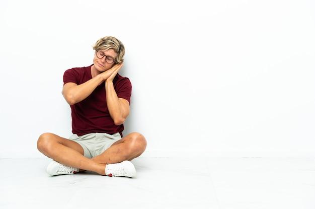 Młody anglik siedzi na podłodze, czyniąc gest snu w dorable wypowiedzi