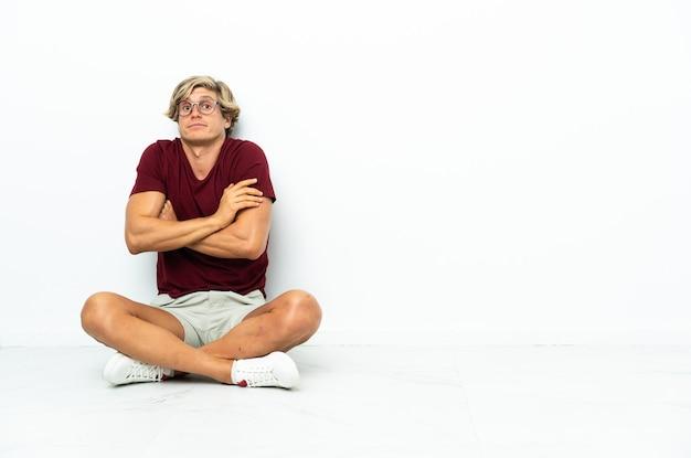 Młody anglik siedzi na podłodze, czyniąc gest wątpliwości