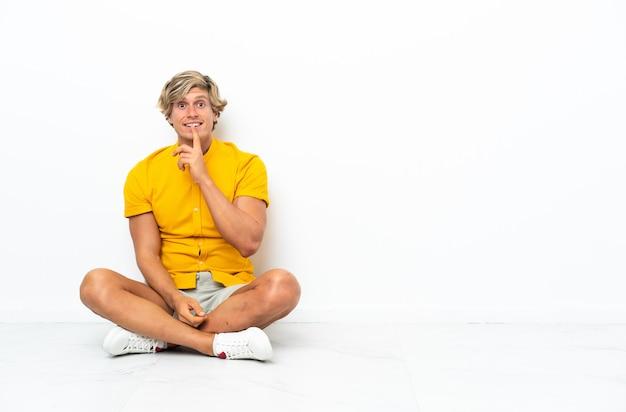 Młody anglik siedzi na podłodze pokazując znak gestu ciszy wkładając palec do ust
