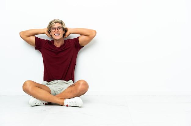 Młody anglik siedzi na podłodze ze śmiechu