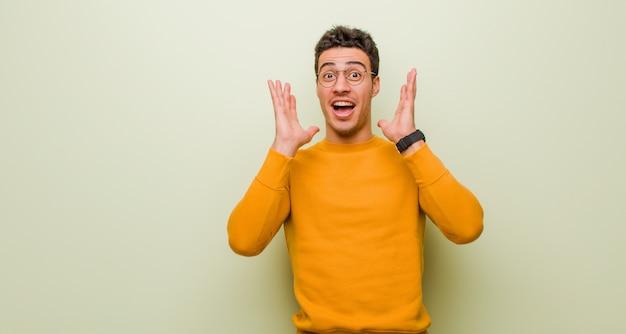 Młody arab czuje się zszokowany i podekscytowany, śmiejący się, zdumiony i szczęśliwy z powodu niespodziewanej niespodzianki na płaskiej ścianie