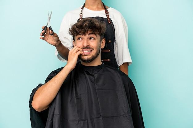 Młody arab gotowy do fryzury na białym tle na niebieskim tle gryzie paznokcie, nerwowy i bardzo niespokojny.