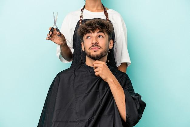 Młody arab gotowy do fryzury na białym tle na niebieskim tle patrząc w bok z wyrazem wątpliwości i sceptyczny.