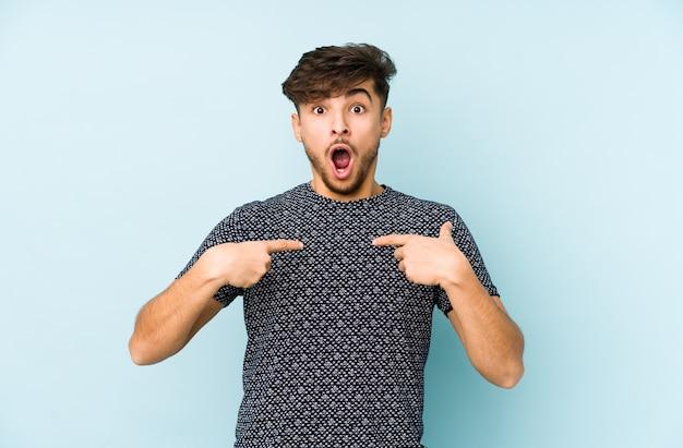 Młody arab mężczyzna na białym tle na niebieskiej ścianie zaskoczony wskazując palcem, uśmiechając się szeroko.