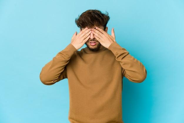 Młody arab na niebieskiej ścianie boi się zakrywających oczy rękami