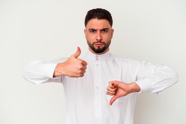 Młody arab ubrany w typowe arabskie ubrania na białym tle pokazując kciuki w górę i w dół, trudno wybrać koncepcję