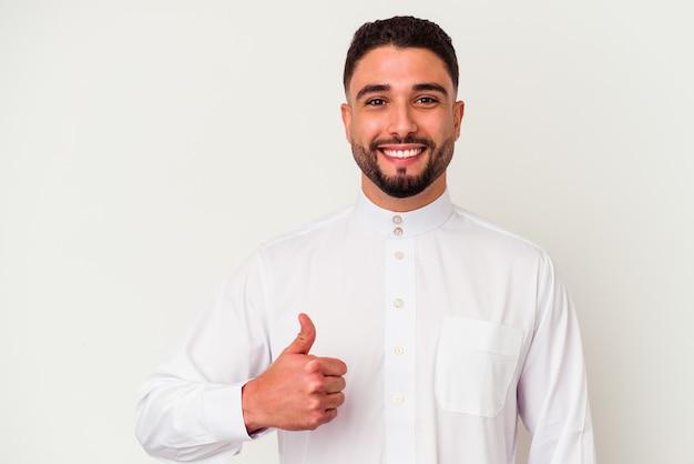 Młody arab ubrany w typowe arabskie ubrania na białym tle, uśmiechający się i podnoszący kciuk do góry