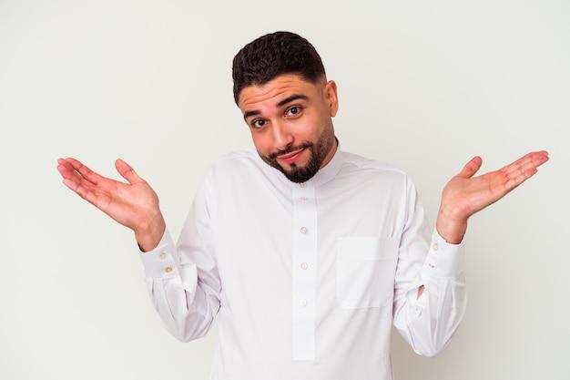 Młody arab ubrany w typowe arabskie ubrania na białym tle wątpi i wzrusza ramionami w pytającym geście.